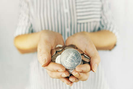Woman hand holding a handful of coins bitcoins on white background. Risky currency mining concept and earnings.