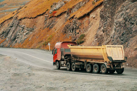Truck carrying bulk materials moves along a road on the mountains highway