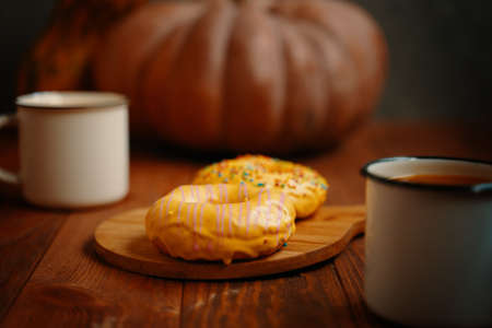 Autumn composition with metal mugs, donuts and pumpkin on a wooden background. Doughnuts with yellow lemon glaze and colorful sprinkles. Sweet pastries on a wooden tray.