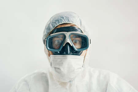 Virologist in a protective suit with a scared look on a white background. Male professional in hooded suit for bio-hazard protection. Banque d'images
