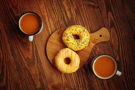 Top view of the autumn composition. Two metal mugs of pumpkin juice and two sweet doughnuts with yellow glaze and sprinkles. Breakfast on a wooden background.