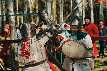 Battle of knights in armor on swords in front of the audience. Festival of historical clubs in the Park. Reconstruction of medieval battles. Bishkek, Kyrgyzstan - October 13, 2019 新闻类图片