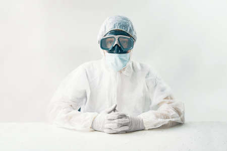 Man in white hazmat on white background studio. Person in a protective suit mask and gloves sits at a table and looks at the camera. 免版税图像