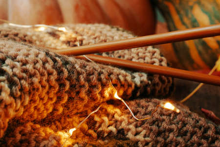 Composition with yarn, wooden needles, lights and colorful pumpkins in the background. Knitting with green brown yarn.