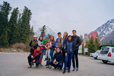 International mountain day concept. Tourists near the hotel pose. Group photo of hikers. Bishkek, Kyrgyzstan - April 9, 2019: