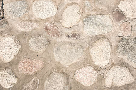 Texture of a stone wall. Natural texture of the rubble wall. The seam of the cement between the rocks. Natural stone background.