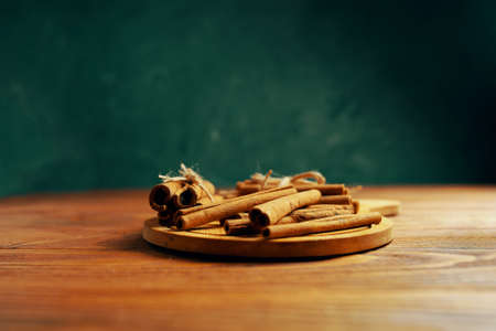 Cinnamon sticks on a tray. Spice on a wooden table. Dark green background. Added to mulled wine or Christmas drinks and baked goods.