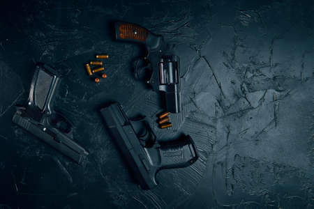 A pistols and copper bullets on black concrete table
