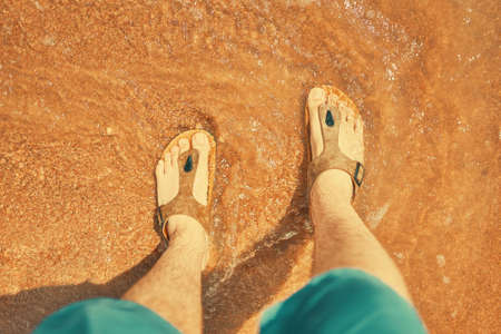Person in jeans shorts stands and looks down at his feet in sand that washes by sea. Mens feet in flip flops sandals on ocean beach. Summer mood. Rest at resort.