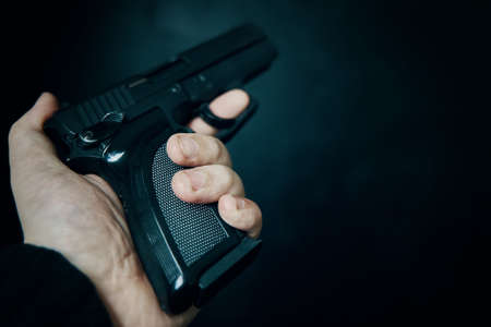 Criminal holding gun on black background. First person view of pistol. Firearm in mans hand. Defense or attack. Murderer or armed thief.