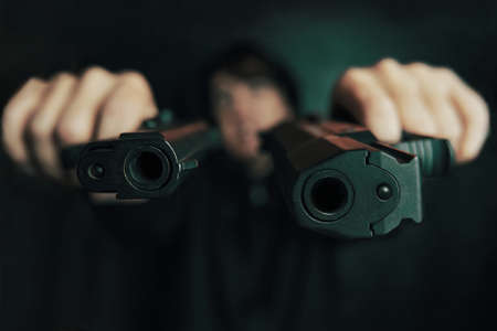 Close-up of two gun muzzles. Guy threatens with firearm. Two pistols in mans hands are pointed at camera. Criminal with weapon.