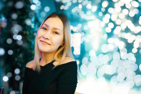 Portrait of awesome woman against background of bright lights. Female posing at camera in lounge bar. Copy space for text or advertisement. Night holiday party. Stockfoto