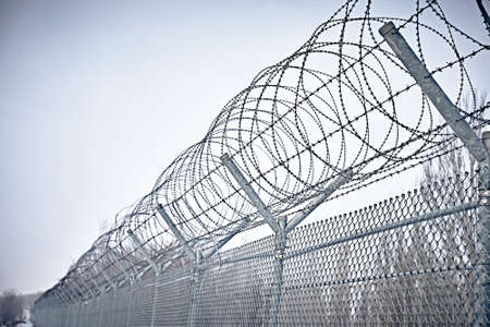 Prison fence. Grid fence with barbed wire against sunset. Barbed wire. Security measures for prisoners in prison.