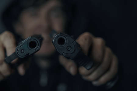 Close-up of two gun muzzles. Man threatens with firearm. Criminal with weapon. Two pistols in mans hands are pointed at camera. Banque d'images