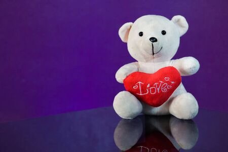 side table: Teddy bear with heart sitting on the glass with  purple background. Get Taste Forever Valentine. Stock Photo