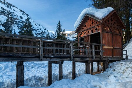 The Tyrolean-style hut and the wooden pier of Braies Lake. In winter the surface of the lake is frozen. The wood of the building is seasoned and discolored from the weather. South Tyrol, Italy. Stock Photo
