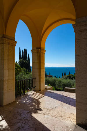 The arches of the Vittoriale degli Italiani overlook Lake Garda. The buildings are light orange and ocher, colors that create a wonderful contrast with the deep blue of the water. Gardone Riviera. 免版税图像