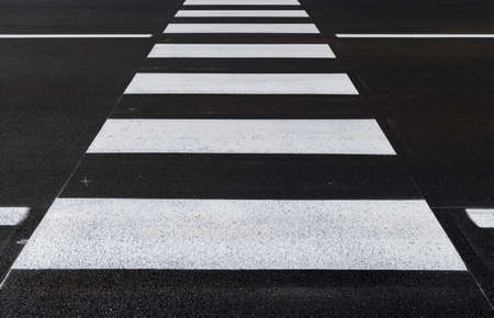Front view of the pedestrian crossing, asphalt road, white stripes on a dark gray background, zebra stripes, perspective views, black and white, high temperature resistant draining asphalt.