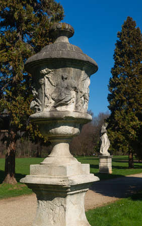 A stone sculpture in the public park of Vicenza: Parco Querini. On the surface scenes of Greek mythology are reproduced. Soft stone with traces of fossil shells. In the background a feminine statue. Banco de Imagens