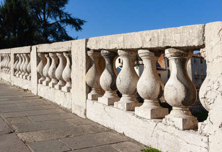 A long stretch of the elegant balustrade of the Ponte San Michele in Vicenza. This structure is inspired by the bridges of Venice. In the background a glimpse of the buildings of the historic center.