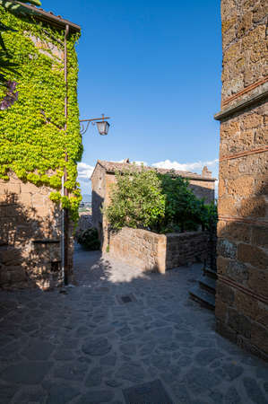 View of the Picturesque Medieval Stone buildings in Civita di Bagnoregio, the village set in the clouds, known as The Dying Town, on the top a plateau of volcanic tuff. Lazio Italy.