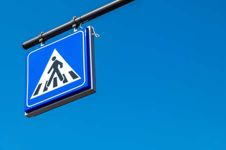 Square shaped pedestrian crossing road sign in blue color with a walking man drawn in a triangle. Pedestrian transit traffic sign on blue sky background.