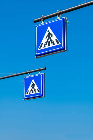 Two blue color square shaped pedestrian crossing road signs with a walking man drawn in a triangle. Pedestrian transit traffic sign on blue sky background.