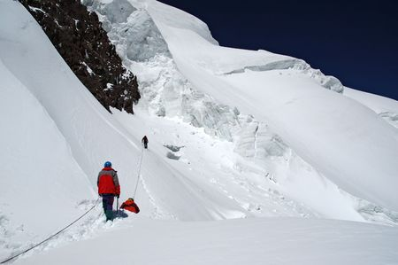 achievment: Group of mountaineers carefully advances through a dangerous place