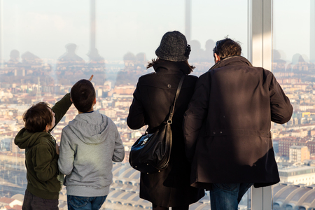 observes: Family observes the city from the window of the skyscraper