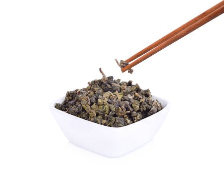 Tea leaves in a cup isolated on a white background.