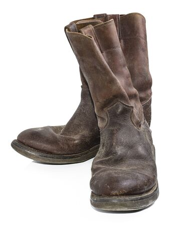 A pair of old, dirty, brown cowboy boots that are separated on a white background. 写真素材