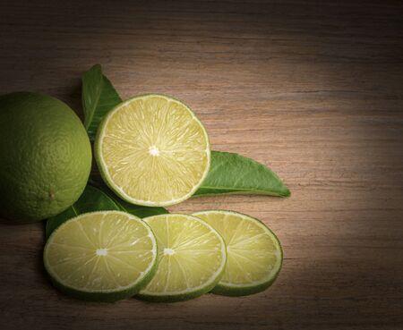 Fresh green lime sliced on wood background. Stockfoto