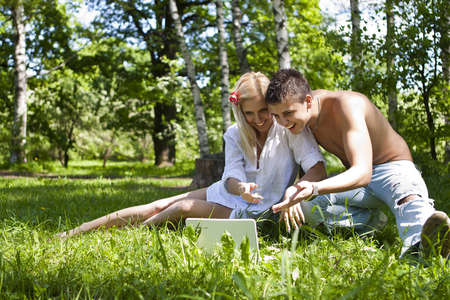 A young couple in love in a park with a laptop