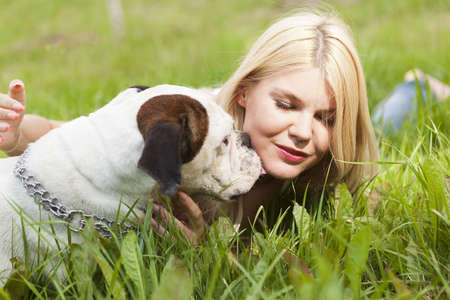 Attractive blonde plays with her dog, a boxer Stock Photo