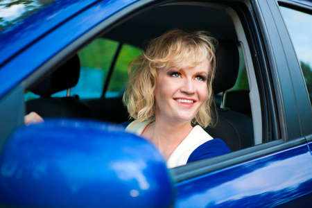 blonde girl at the wheel of blue car