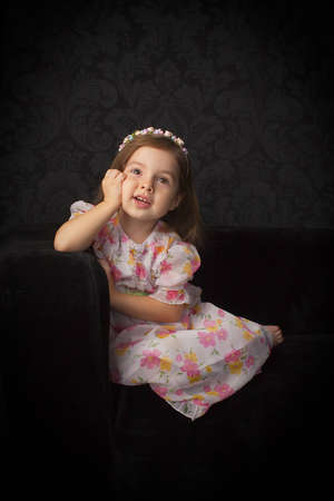 Little girl look up and sitting on the sofa
