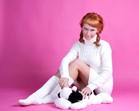 Portrait of a red-haired girl in a white sweater with a soft toy Stock Photo
