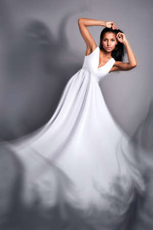 portrait of a beautiful dark-skinned woman in a white dress in the studio photo