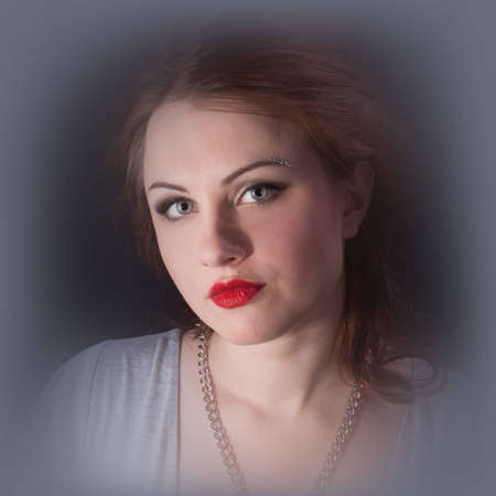 Portrait of a red-haired girl with red lips in a gray dress