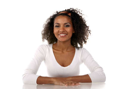 portrait of a beautiful smilling dark-skinned woman in a white dress in the studio Stock Photo