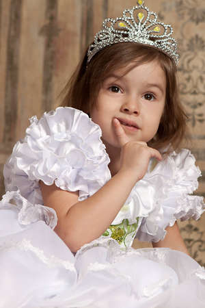 little cute girl in white dress with a tiara on her head photo