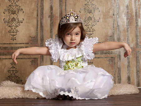 little cute girl in white dress with a tiara on her head
