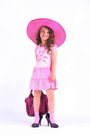 Little girl in a beautiful rose dress with pink hat and bag Stock Photo