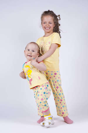 two cute girls in pink pajamas in the studio