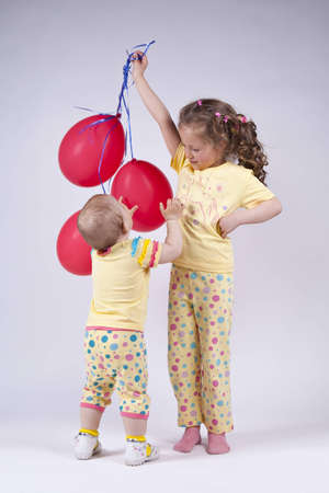 two cute girls in pink pajamas in the studio playing with red balloons Stock Photo - 12574454