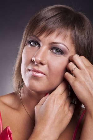 closeup portrait of brunette girl in pink dress in studio
