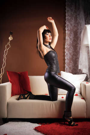 Portrait of a brunette posing in a leather jumpsuit in a room on a white sofa photo