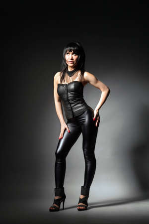 dark haired woman: Portrait of a brunette woman posing in a leather jumpsuit in the studio