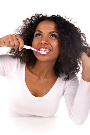 Portrait of a beautiful black woman cleaning her teeth in the studio photo