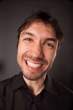 grimacing: closeup portrait of grimacing man in black shirt